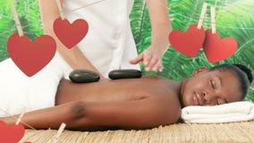 Masseuse устанавливая горячие камни массажа на задней части черной женщины на спа на день Валентайн акции видеоматериалы