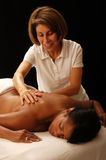 Masseuse and client. A masseuse massages a client on the table Stock Image