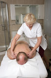 Masseuse and client in treatment room Royalty Free Stock Photos