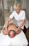 Masseuse and client in treatment room Stock Photos