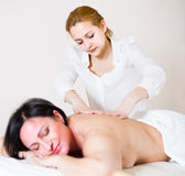 Masseuse is doing healthy massage of back and loin to adult woma Stock Images