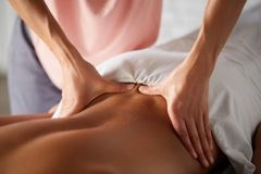 Masseuse doing massage for male client royalty free stock photo