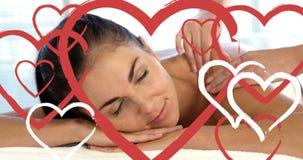 Masseuse faisant le massage aux femmes attirantes décontractées à la station thermale avec des coeurs pour le jour de valentines  banque de vidéos