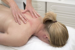 Masseuse giving a back massage to a client Royalty Free Stock Image