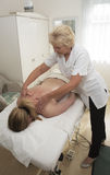 Masseuse giving a back massage to a client Stock Photo