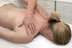 Masseuse giving a back massage to a client Royalty Free Stock Photography
