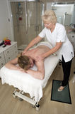 Masseuse giving a back massage to a client Stock Photos