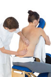 Masseuse giving back massage to naked woman Stock Images