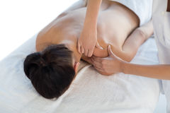 Masseuse giving back massage to naked woman Royalty Free Stock Photography