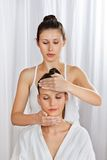Masseuse Giving Head Massage To Woman. Female masseuse giving a head massage to women at health spa Royalty Free Stock Photo