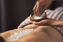 Body scrub with salt at spa. Masseuse hands doing massage on woman`s back at beauty salon. Beauty therapist pouring salt scrub on women back at health spa stock photography