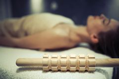 Masseuse lying on massage bed. With massage roller by her side Stock Photos