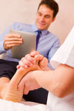Masseuse massaging businessman's foot Royalty Free Stock Image