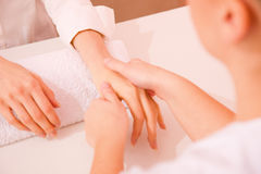 Masseuse massaging hand Royalty Free Stock Image