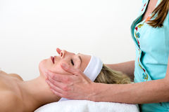 Masseuse performing a facial massage on a woman. Royalty Free Stock Photography