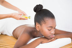 Masseuse pouring massage oil on a pretty woman back. Masseuse pouring masage oil on a pretty woman back at the health spa Stock Photography