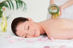 Masseuse pourring massage oil o. N a young woman's back in a spa royalty free stock images