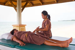 Masseuse at work on the beach in Thailand Stock Photo