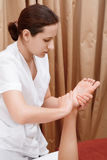 Masseuse works with feet and legs Royalty Free Stock Image