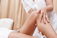 Masseuse works with feet and legs. Slim legs. Close-up of a masseuse massaging legs of a young women in spa center Stock Images