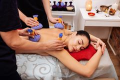 Two experienced women in black uniform working with special equipment. Masseuses processing. Two experienced women in black uniform working with special royalty free stock photography
