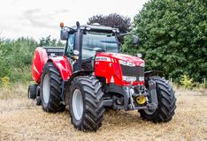 Massey Ferguson 7618 parked up with baler. A Red modern Massey Ferguson tractors 7618 parked up near hedge with baler stock photography