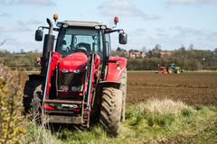 Massey Ferguson parked up with tractor drilling in background Stock Image