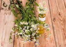 Massez l'huile dans une bouteille en verre avec des fleurs de camomille sur en bois merci Images stock
