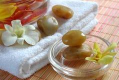 Massez les pierres, l'essuie-main, l'orchidée et l'eau parfumée Image stock