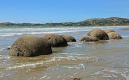 Massi di Moeraki nell'alta marea Fotografie Stock