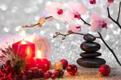 Massieren Sie Zusammensetzungsweihnachtsbadekurort mit Kerzen, Orchideen und schwarzen Steinen Stockbild