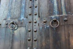 Massieve oude zwarte doorstane staaldeur met loperslot Stock Fotografie