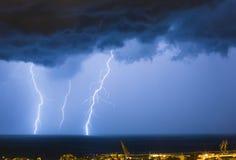 Massieve wolk om bliksembouten aan de grond te zetten die de horizon van stadslichten raken stock afbeeldingen