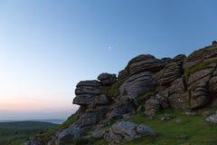 Massif de roche de Dartmoor avec la lune ci-dessus Photo stock