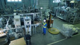 Massiv enhet av en fabrik producera plast- skyttlar med en manlig arbetare i den arkivfilmer