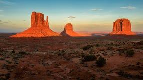 Massiva sandstenpelare skjuta i höjden ovanför den iconic monumentdalen på solnedgången Fotografering för Bildbyråer