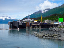 A massive barge secured at valdez. The oil industry protecting the marine environment with the use of oil booms Royalty Free Stock Images