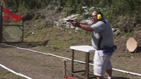 Man fires automatic handgun pistol during training in practical shooting. Massive body Man fires automatic handgun pistol during training in practical shooting stock footage