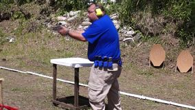 Massive body Man fires handgun during practice training in practical shooting. San Pablo City, Laguna, Philippines - July 29, 2013: Massive body Man fires stock footage