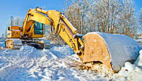Massive bulldozer, work stopped for winter. Massive bulldozer in snow, work delay due to cold weather Stock Photos
