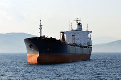 Massive cargo ship. A massive cargo ship floating on a calm sea royalty free stock photo