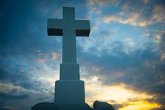 Christian cross in the blue sky. Massive Christian cross in the blue sky made from stone stock image