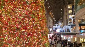 Massive Christmas Tree Lighting The Way for Shoppers in a Mall stock images