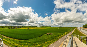 Green, yellow field forest and clouds on blue sky in summer, sunny day. Royalty Free Stock Images