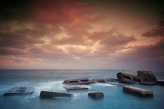 Massive concrete blocks form a breakwater with soft blur sea royalty free stock image