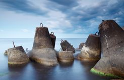 Massive concrete tetrapods form a breakwater with soft blur sea royalty free stock photography