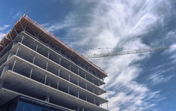 Massive crane assists on high rise construction site Royalty Free Stock Photo