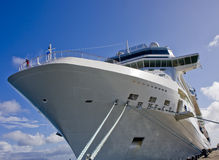 Massive Cruise Ship Tied to Dock. A large white cruise ship tied to a dock with rope Stock Images