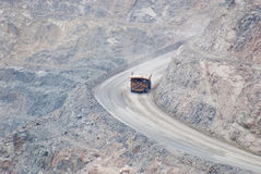 Massive dump truck moving downhill on whide and steep road. Huge mining dump truck moving down into a digged super pit. those machines are used for carring tons Royalty Free Stock Images