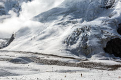 Massive Glacier at High Altitude Severe Mountains and Small Body of Alpine Climber Walking Royalty Free Stock Photos